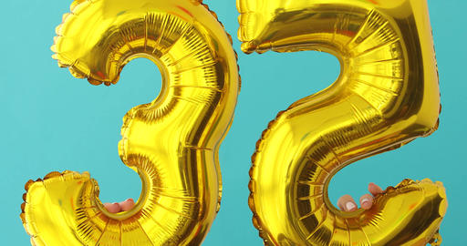 Gold foil number 35 celebration balloon on a blue Footage