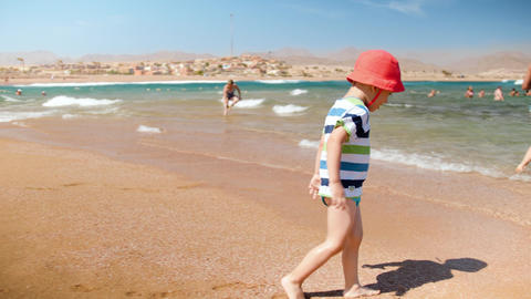 4k slow motion video of cheerful 3 years old toddler boy playing on the sea Footage