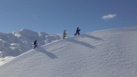Aerial - Snowboarders and a skier walking uphill Footage
