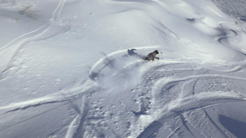 Slow motion - Aerial shot of snowboarder riding in powder snow and joining other Footage