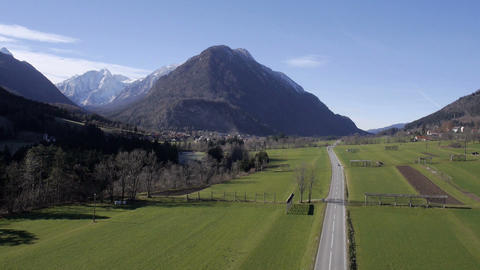 Aerial - Highland landscape with car road and snowy mountains Footage