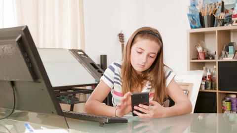 Bored teenage girl sits at a desk and surfs the internet on her smartphone Footage