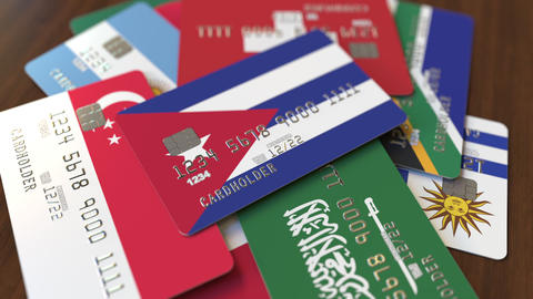 Many credit cards with different flags, emphasized bank card with flag of Cuba Footage