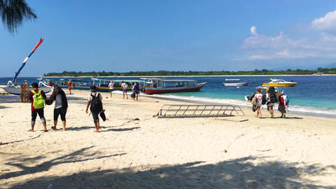 Gili Trawangan, Indonesia, 20 Mar 2019 - Tourists walking on Sandy beach with Footage