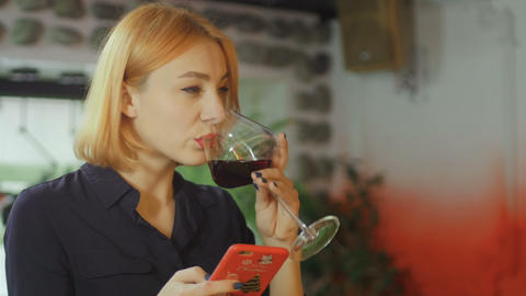 Woman Drinking Wine And Using Smartphone In Bar Live Action