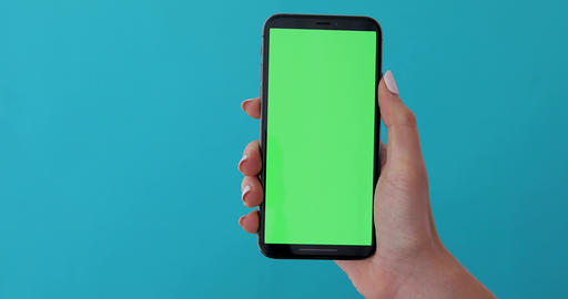 Woman hand holds a smartphone with greeen screen Live Action