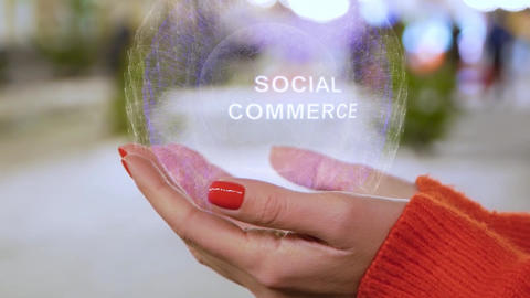 Female hands holding hologram with text Social commerce Footage