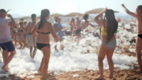 4k slow motion out of focus video of cheerful people dancing the foam while Footage