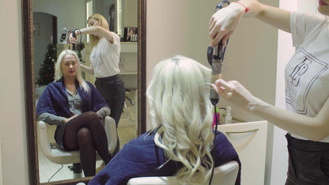 Hairstylist curling woman's hair using hair iron Stock Video Footage