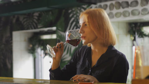 Pretty woman drinks wine and smiles to the bartender Stock Video Footage