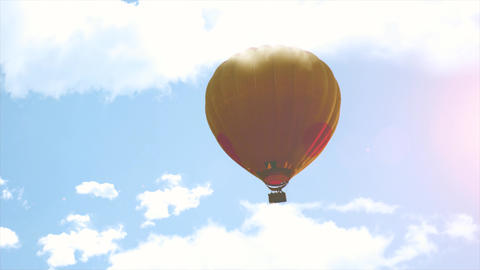 Hot Air Balloon is flying on sky between clouds and sunlight. Trip with basket which working fire Footage