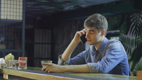 Young man talking on cellphone and drinking alcohol Live Action