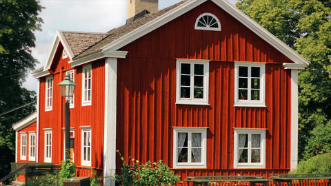 Red, wooden detached house. Nordic style, old, historical beautiful home in grass, nature with Footage