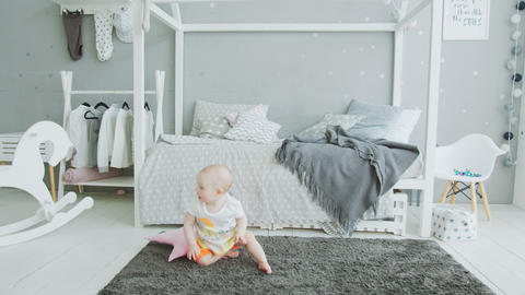 Cute baby trying to get up from floor at home Footage