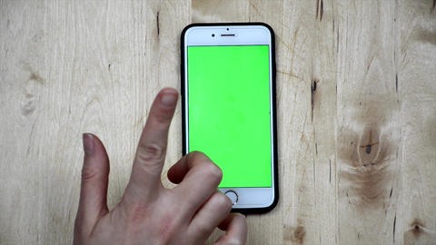 Woman is using smartphone with green screen. Girl's hand using, holding phone. top view. Blank, Footage