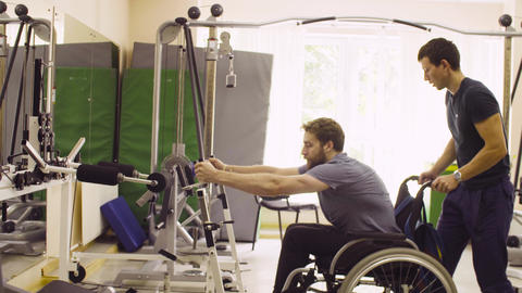 Disabled man doing strength exercises for hands in the rehabilitation clinic Live Action