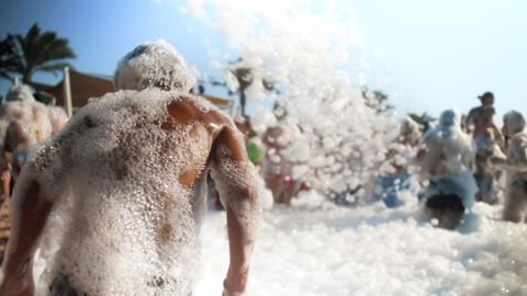 4k blurred video of cheerful crowd dancing on the soap beach party. Soap bubbles Live Action
