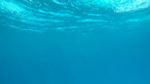 Beautiful under water video of dark blue sea water and sun ray shining through Footage