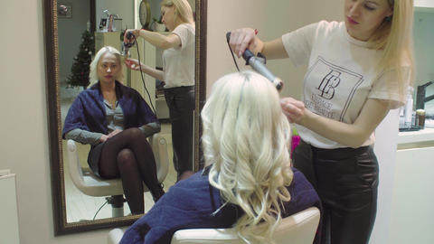 Hairstylist curling woman's hair using hair iron Live Action
