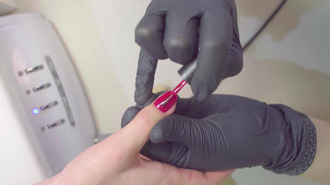 Hands of manicurist applies shellac to the client Live Action