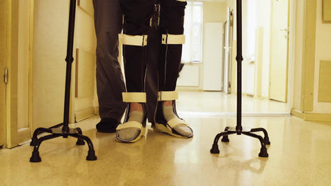 Legs of invalid in orthosis walking with support of two walking cane Live Action