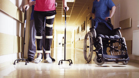 Close up legs of disable man in orthosis walking with support of two walking Live Action