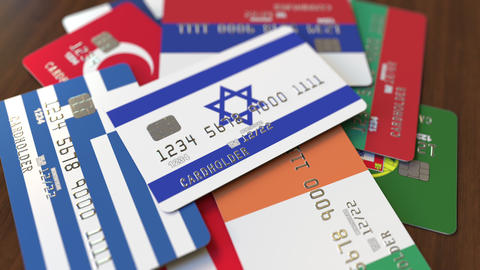 Many credit cards with different flags, emphasized bank card with flag of Israel Live Action