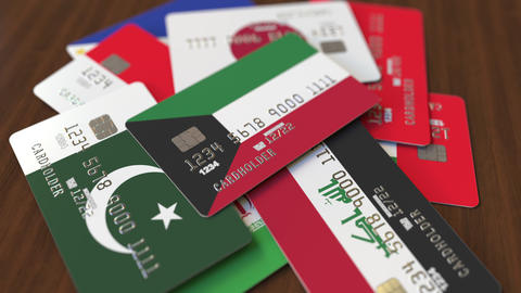 Many credit cards with different flags, emphasized bank card with flag of Kuwait Live Action
