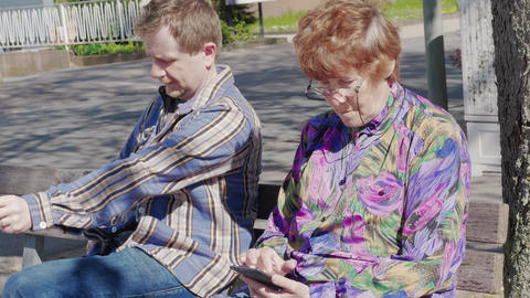 Neighbours on bench with mobile phones outdoor, emotions Footage