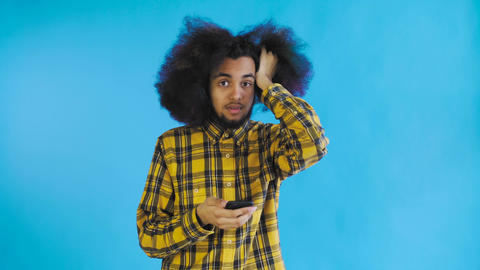 Young sad Afro-American man using phone and getting bad news on Blue background Live Action