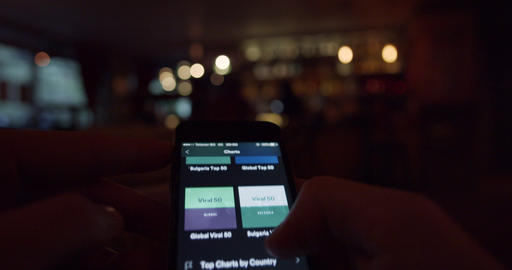 Smartphone user browsing musical charts from Spotify music application Footage