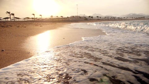 Extreme slow motion video of sea waves rolling on the golden sand beach at Footage