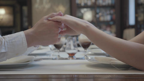 Males hands holding ladys hands. Romantic date of man and woman in the Footage