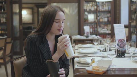 Portrait cute woman in the suit sitting in the restaurant eating fast food Footage