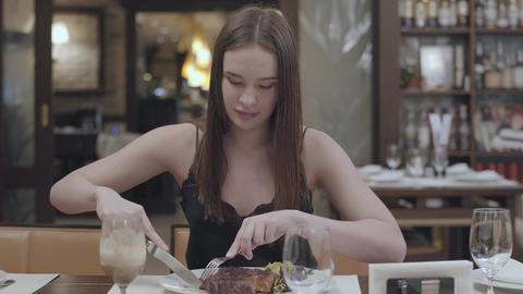 Portrait of young woman cutting tasty steak lying with vegetables and leaves on Footage