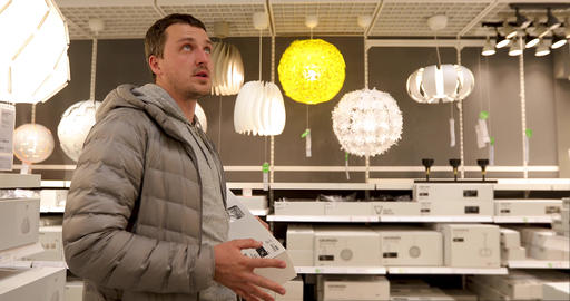 Single man is holding a light bulb in household store Footage