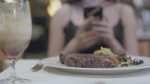 Tasty steak with vegetables and leaves lying on the plate in front of the woman Footage