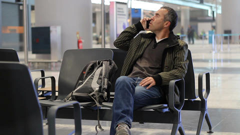 Passenger man talking with phone while waiting for plane in airport passenger terminal Footage