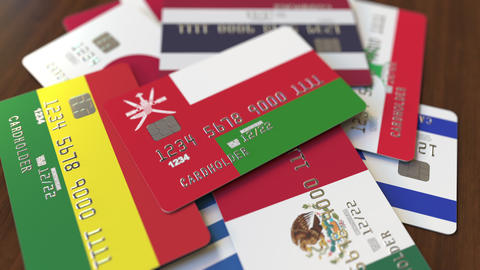 Many credit cards with different flags, emphasized bank card with flag of Oman Footage