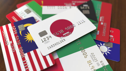 Many credit cards with different flags, emphasized bank card with flag of Japan Live Action
