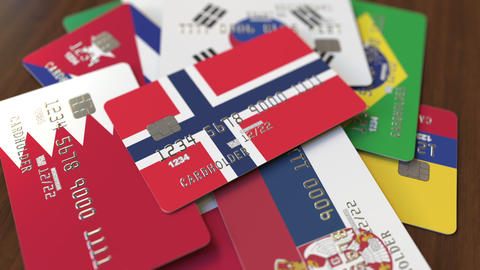 Many credit cards with different flags, emphasized bank card with flag of Norway Live Action