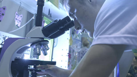 Life scientist working at a laboratory. A student is looking through a Footage