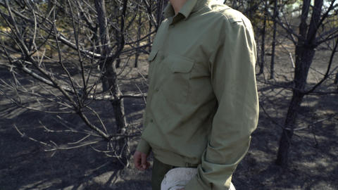 Man in despair putting off his hat standing in burned forest af wildfire Live Action