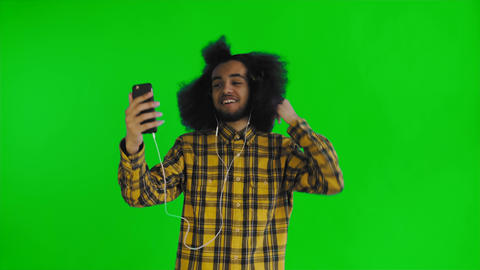Young African American man video calling with phone on green screen or chroma Footage