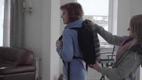 Mature woman in blue hoody fixing black comfortable backpack at her back Footage