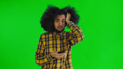 Young sad Afro-American man using phone and getting bad news on green screen or Live Action
