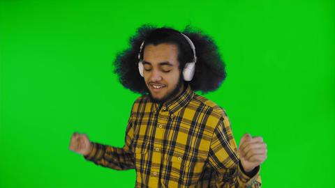 Positive African American man listening music in his headphones on green screen Footage