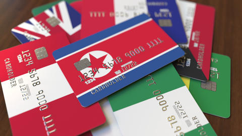 Many credit cards with different flags, emphasized bank card with flag of North Live Action