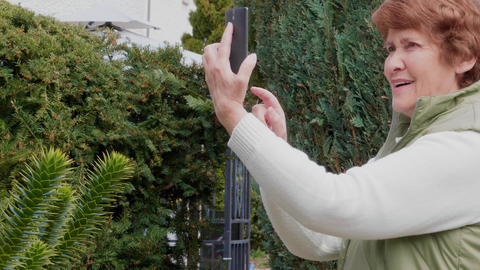 Smiling senior woman taking photos, getting selfie by mobile Footage