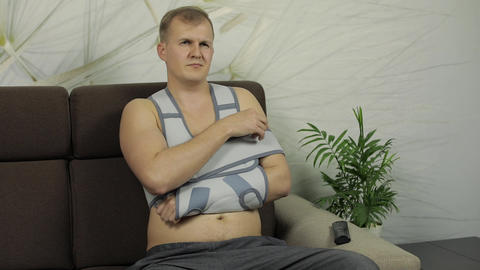 Painful man with a broken arm wearing arm brace sitting… Stock Video Footage